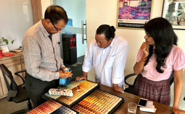 Dev Anand Sarawagi (left) and Shally Sarawagi (right) consult with staff from Sarawagi Rugs' on 17 July 2019 in Kathmandu, Nepal as final colour selections are made for the prototype handknotted rug made from ECONYL® regenerated nylon. | Photograph by The Ruggist.